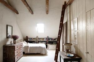 """I sovrummet finns en av två IKEA-möbler i Magnus lägenhet och det är sängen. """"Till mitt försvar så köpte jag en säng med naturmaterial med tagel. Den bästa Ikea-sängen.""""Bredvid står en byrå i rött för ovanlighetens skull. Magnus föredrar gråtoner. Den är ett provinsarbete som är målad för att efterlikna Stockholmsarbeten i mahogny. Den röda färgen är original från cirka 1810.Spegeln ovanför är fransk och har originalfärg och glas.Det vackra bordet kommer från Småland och är aldrig övermålat. Det har stått i ett hem och har fått vara i fred.  Framtill ses en vacker skrapning. """"Det är inte vilket bord som helst utan har haft stor betydelse för någon"""", säger Magnus.Ovanpå står en fransk stenkruka från 1800-talet."""