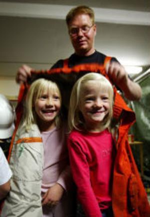 Robert Andersson hjälper Josefine Edman och Olivia Lindgren att prova en äkta brandmansjacka.
