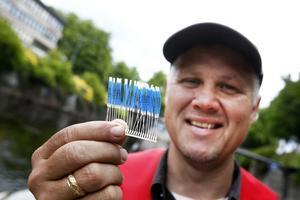 Fiskforskare Mikael Carlstein visar upp plastremsorna som sätts fast under fiskarnas ryggfenor.