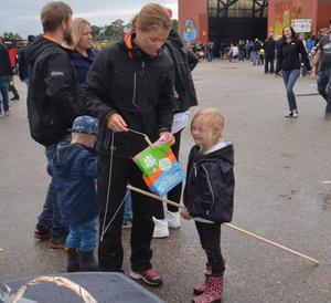 Tindra Ramberg från Uppsala får hjälp av mamma Jeanette vid fiskdammen medan de väntar på att pappa Anders ska köra nästa heat med sin crosscart.
