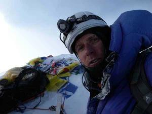En mycket trött men nöjd Fredrik Sträng på Lothses topp. Klättringen upp skedde i mörker, därav pannlampan.