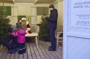 Självaste tomten tar emot i sin egen bod på Tomasmarknaden, även om vissa besökare är tveksamma inför mötet.   Foto: Anders Pihl