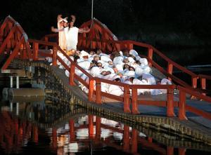 Sommarnattsdans på Österfors flottbro. Här ses dansarna på en av de karaktäristiska flottningspucklarna, samtidigt som bilden visar att flytkraften försämrats så att träpartier ligger i vatten och därmed rötskadas. Foto:Kent Olsson