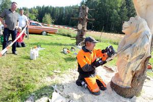 Hans-Erik Hansson från Ljusdal går loss med sin motorsåg. Några skär här och några skär där och med ens börjar konturerna av en björn att träda fram i stocken. Ovanför björnens huvud har redan två ugglor snidats fram ur träkonstnärens skickliga händer.