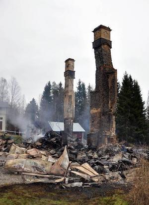 Endast en stensockel och två skorstenspipor återstår av den brunna byggnaden.  Foto: Ingvar Ericsson