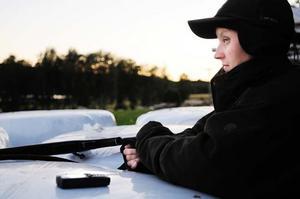 Katarina håller koll på klockan på mobiltelefonen, räven brukar vara punktlig.