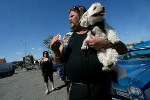 Big Papa, Mikael Bergström från Umeå med hunden Backus som har en egen skinnväst.—Den här hunden älskar att åka raggarbil. När västen åker på så vet han att det är dags, säger husse Big Papa.I Västerås kommer över 10 000 bilägare träffas. Att köra i karavan dit innebär en trygghet om bilen inte skulle hålla hela vägen. Annette Bergström i bakgrunden.