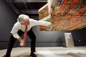 En representant för hamnmyndigheten i New York pekar på budskap skrivna på World Trade Center. Den 62 kilo tunga pelaren ställs ut på det nya museet.