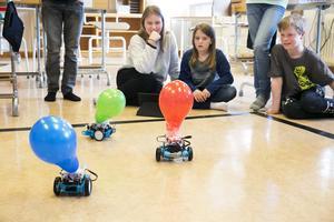 Josefin Larsson, Miranda Johansen och Oscar Gustafsson tittar på robotkriget och hoppas deras ballong ska klara sig helskinnad.