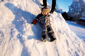 """Treåriga Simon Asprot leker glatt i snöhögen i Badhusparken. """"Vi bor i Stockholm men jag är härifrån, så det är roligt med riktig vinter"""", säger pappa Robert Asprot som har köpt löskragar åt både sig och sonen för att inte frysa."""