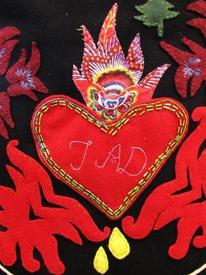 Ett brinnande, blödande hjärta från Hälsingland. Detalj ur förkläde av Ida Björs.