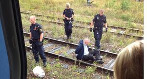 Polisen placerade den hotfulle mannen på rälsen utanför tåget efter ingripandet.