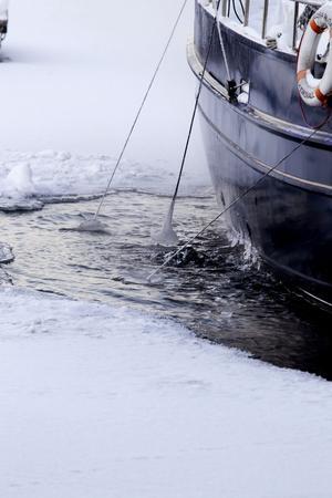 En strömbildare håller isfritt runt en båt i hamnen.