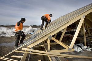 Ola Persson och Henrik Lusth jobbar uppe på taket som ligger på marken vid Hudiksvalls flygfält.