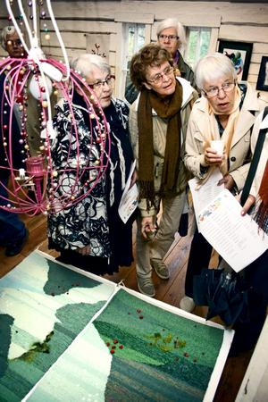 Från Karlsborgs konstförening: Gunborg Lundkvist, Siv Nerlich och Gunnel Landelius beundrar lingonmattan av Åsa Westerberg och Eva Borg.
