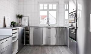 Köket har luckor i rostfritt och kaklade väggar från golv till tak. Foto: Hoome mäkleri