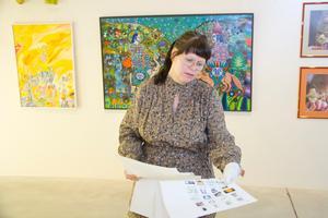 Maja-Lena Molin med målningar av Madeleine Pyk i bakgrunden.