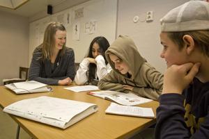Jenny Sjöberg med några av sina elever i klass 8 d: Golbarg Kharaghani, Leo Bergkvist och Benjamin Olsson som just håller på med läxläsning.