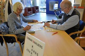 Två gånger i veckan bänkar sig Gunnar Wahlberg på biblioteket för att ge korsordshjälp. Här löser han klurigheter tillsammans med Eva Hellsten. Bild: JAN WIJK