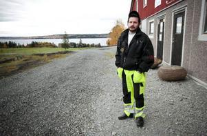 Nils Björid vid den nya ladugården i Slandrom. I bakgrunden syns Östersund.