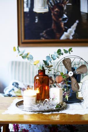 Att arrangera små stilleben hemma är ett enkelt sätt att skapa trivsel på. En gammal fläkt är dekorativ, men ska den användas bör man kosta på att elrenovera den. Medicinflaskor blir fina vaser.