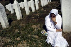 En kvinna sörjer vid sin släktings gravsten vid minnesplatsen i Potocari, en av alla de som mördades vid Srebrenica. Arbetet med att identifiera och begrava kropparna som hittades i massgravar har pågått i åratal.