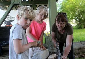 Ivan Öst och Loe Bohlin provar på stenskulptering tillsammans med Ragnhild Sandelius Brodow.