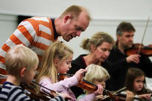 Henrik Ottosson hjälper till att instruera dottern Anna. Både barn och föräldrar kan hyra instrument hos kulturskolan.