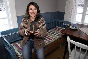 Den här soffan fanns i stugan då Dan Andersson skulle ha flyttat in. Maria Norgren tittar i boken där Dans hustru Olga bland annat noterat att hon betalde 20 kronor i månaden i hyra för stugan.