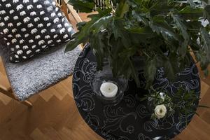 Detaljbild från vardagsrummet. Kudde från Svensk tenn. Stol från Swedese. Brickbord med vas från Annaviktoria.