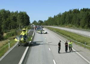 E 18 stängdes av under räddningsarbetet. Mc-föraren överlevde, men är ännu inte helt återställd. Foto: Räddningstjänsten