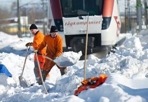 Banarbetare skottar tågväxlar rena från snö på bangården till järnvägsstationen i Hallsberg.