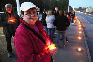 Leene Gloel tänder ett ljus, i bakgrunden maken Helmut.