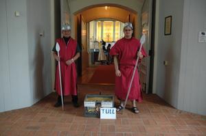 Tull. Publiken stoppades av dessa två barska Romerska soldater som krävde tull. De om inte hade något att ge fick deponera sina skor i kartongen.