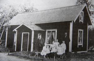 Saltharsfjärden 1910. Stugan har byggts om, och här sitter Hildur i sin mammas knä.
