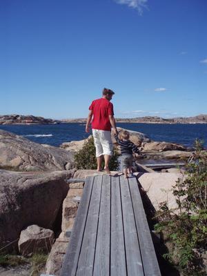 Arvid, två år, och pappa Kjelle Valsås på väg mot nya horisonter. Far och son går på upptäcksfärd på spångarna på S:t Göransö, juli 2011.