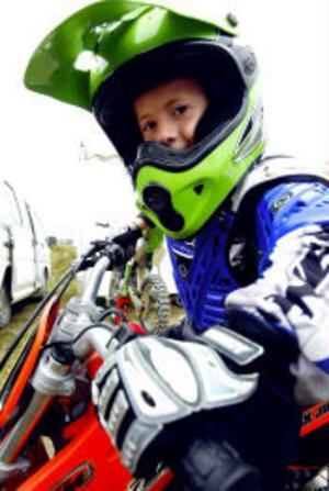 Sebastian Nordlander i full motocrossmundering. Hjälmen ser hemskt tung ut men väger mindre än den ser ut att göra. Än så länge kör han i minsta klassen, 50 kubik. Men med en hel familj engagerad i sporten lär han visa sig bland de stora grabbarna om några år.