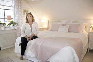 Pastellrosa accentfärg i sovrummet är ett av få undantag i Carinas inredning.