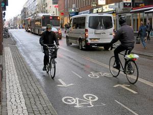 Ny cykelväg. På ena hållet får cyklisterna bussar och bilar till höger om sig.
