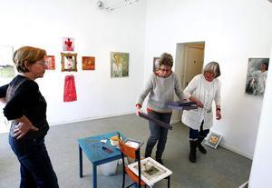 Barbro Bäck, Eva Sollander och Lena Backman i färd med att kombinera bilder av 29 kvinnliga konstnärer på bästa sätt.