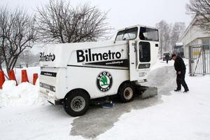Ismaskinen, den så kallade Rolban, kör längs banan och släpper vatten som ska frysa till is. Hans-Inge  Jonasson kör maskinen medan Stig Söderqvist granskar att det blir rätt.