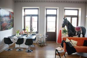 Rolfcarlwerner, stolar med trumpetfot och hästen Fhesten bakom den orange soffan.