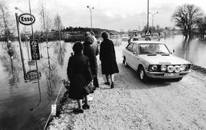 Den här bilden tog Rolf Karlsson vid södra infarten till Lindesberg och dåvarande macken Esso. Många kom för att titta på översvämningen, däribland damerna på bilden.