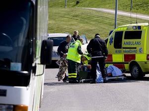 Cyklisten tas om hand av ambulanspersonalen.
