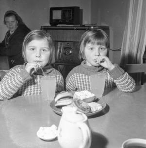 6-åriga tvillingarna Maj och Ulla Moberg läskar sig med saft och bulla.
