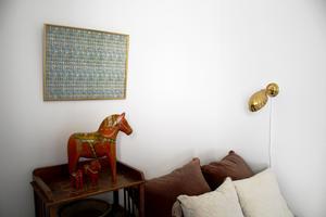 De extremt trendiga snäcklamporna är arvegods. På väggen hänger en tavla med gamla frimärken.