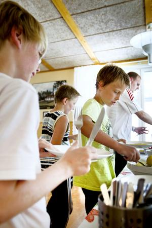 LUNCH. Gabriel, 10 år, Anton, 11, Jakob, 10 och fritidsledaren Michael Swarbrick tar för sig av fiskpinnarna.