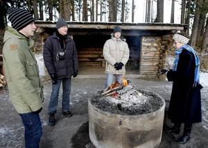Värmande brasa. David Andersson, Ola Andersson och Johan Byström har gjort upp elden som Gunilla Lindström värmer sina frusna händer över.
