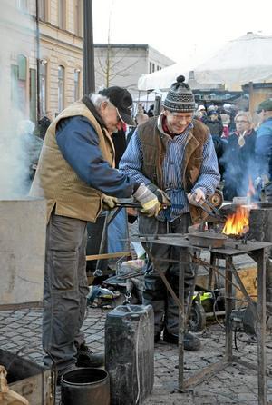 K-G Karlsson och Lennart Larsson, från Nora Bergslags smidesförening, smider medan järnet är varm.