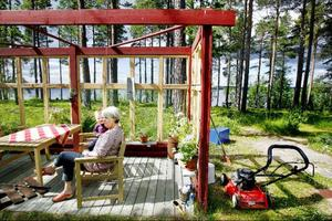 Vivi Nässén och barnbarnet Johan Carnebrandt sitter på altanen utanför fritidshuset i Västbyn och njuter av sommaren.